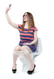 Funny girl photographs herself sitting on the toilet. Stock Photography