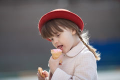 Funny girl with pigtails in hat  eating ice cream Royalty Free Stock Photo