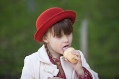 Funny girl with pigtails in hat  eating ice cream Royalty Free Stock Photography