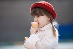 Funny girl with pigtails in hat  eating ice cream Stock Images