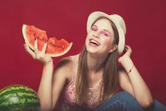 Funny girl with pink make up, wearing jeans, hat and top, posing at red studio background, holding slice watermelon, looking at. Camera and smile emotionally stock images