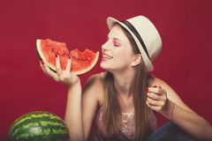 Funny girl with pink make up, wearing jeans, hat and top, posing at red studio background, holding slice watermelon, looking on. Side and smile emotionally stock photos