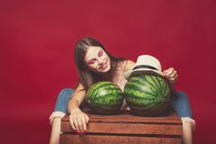Funny girl with pink make up, wearing jeans, hat and top, posing at red studio background near wooden box, holding few watermelon. Looking at camera and smile stock photo