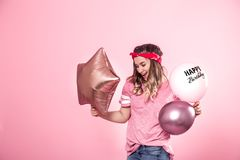 Funny girl in a pink t-shirt with balloons Happy Birthday gives a smile and emotions on a pink background. The concept of the party and holiday royalty free stock photo