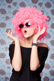 Funny girl in pink wig. And glasses posing for camera across wallpapers background royalty free stock photos