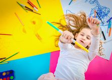 Funny girl play with crayons. stock photo