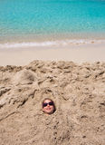 Funny girl playing buried in beach sand smiling sunglasses Stock Photography