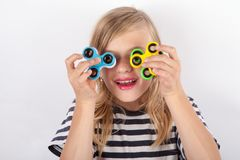 Funny girl playing with four fidget spinners Royalty Free Stock Photography