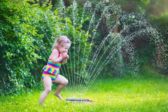 Funny girl playing with garden sprinkler. Funny laughing little girl in a colorful swimming suit running though garden sprinkler playing with water splashes royalty free stock photos