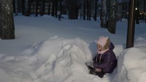 Funny girl playing in snowball during evening walking on winter vacation. Winter activity during Christmas holiday. Happy childhood concept stock video