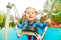 Funny girl portrait on swing set of playground Stock Image
