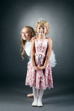 Funny girl posing with her shy little sister Stock Images