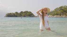 Funny girl posing in sea. Adorable teenage girl in wide-brimmed hat standing in calm blue sea, grimacing and gesturing at summer day stock video footage