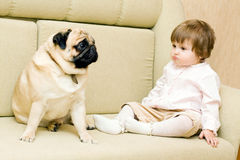 Funny girl with a pug. Funny girl on the couch with a pug Royalty Free Stock Photography