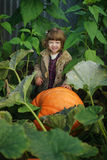 Funny girl with pumpkins in the garden Royalty Free Stock Images