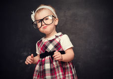 Funny girl pupil in glasses at blackboard Royalty Free Stock Photography