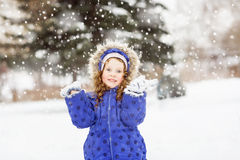 Funny girl raised her hands in the air, catching snowf Stock Photo