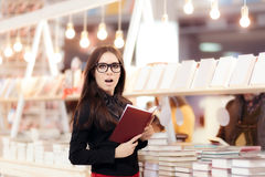 Funny Girl Reading a Book in front of a Bookshelf Stock Images