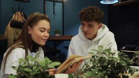 Girl reads her boyfriend a funny excerpt from fiction book and they laugh and smile sitting in coffee house. Funny girl reads her boyfriend a cheer excerpt from stock video footage