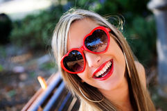 Funny girl with red heart glasses. In a park royalty free stock photos