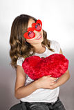 Funny girl with red heart glasses and pillow Stock Photos