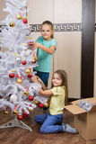 Funny girl remove Christmas decorations with Christmas tree Royalty Free Stock Images