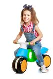 Funny girl riding on a plastic children's Bicycle Royalty Free Stock Photo
