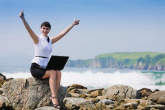 Funny girl on the rocky shore sits Royalty Free Stock Photography