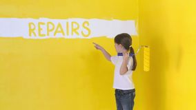 A funny girl with a roller in her hand. Wrote on the wall an inscription repairs stock video