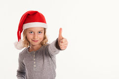 Funny girl with Santa- Claus cap and thumb up Stock Photos