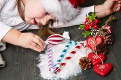 Funny girl in Santa hat Santa near christmas decoration Royalty Free Stock Photo