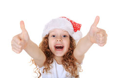 Funny girl in Santa hat showing thumbs up, on light snow backgro Royalty Free Stock Image