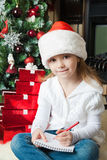Funny girl in Santa hat writes letter to Santa Royalty Free Stock Photo