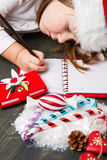 Funny girl in Santa hat writes letter to Santa near christmas de Royalty Free Stock Photography