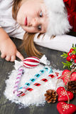 Funny girl in Santa hat writes letter to Santa near christmas decoration Stock Image