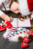 Funny girl in Santa hat writes letter to Santa near christmas decoration Royalty Free Stock Photos