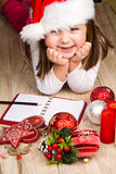 Funny girl in Santa hat writes letter to Santa near christmas decoration Stock Photos
