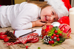Funny girl in Santa hat writes letter to Santa near christmas decoration Royalty Free Stock Photo