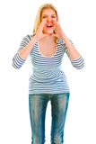 Funny girl shouting through megaphone shaped hands Stock Photo