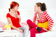 Funny girl showing tongue her amazed girlfriend Stock Photos