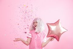 Funny Girl with silver hair gives a smile and emotion on pink background. Young woman or teen girl with balloons and confetti. Concept of holiday and party stock photography