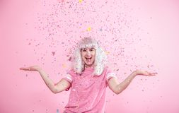 Funny Girl with silver hair gives a smile and emotion on pink background. Young woman or teen girl with confetti. Concept of holiday and party stock photo