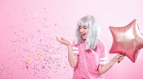 Funny Girl with silver hair gives a smile and emotion on pink background. Young woman or teen girl with balloons and confetti. Concept of holiday and party royalty free stock photo