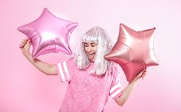Funny Girl with silver hair gives a smile and emotion on pink background. Young woman or teen girl with balloons and confetti. Concept of holiday and party royalty free stock image