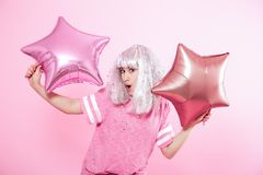 Funny Girl with silver hair gives a smile and emotion on pink background. Young woman or teen girl with balloons and confetti. Concept of holiday and party royalty free stock photos