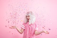 Funny Girl with silver hair gives a smile and emotion on pink background. Young woman or teen girl with confetti. Concept of holiday and party royalty free stock photography