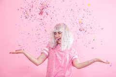 Funny Girl with silver hair gives a smile and emotion on pink background. Young woman or teen girl with confetti. Concept of holiday and party stock photos