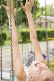 Funny girl sitting on the chair of a swing ride Royalty Free Stock Photography