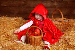 Funny girl is sitting on pile of straw with a basket. Little Red Royalty Free Stock Photo