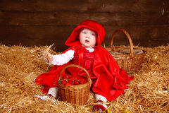 Funny girl is sitting on pile of straw with a basket. Little Red Royalty Free Stock Image